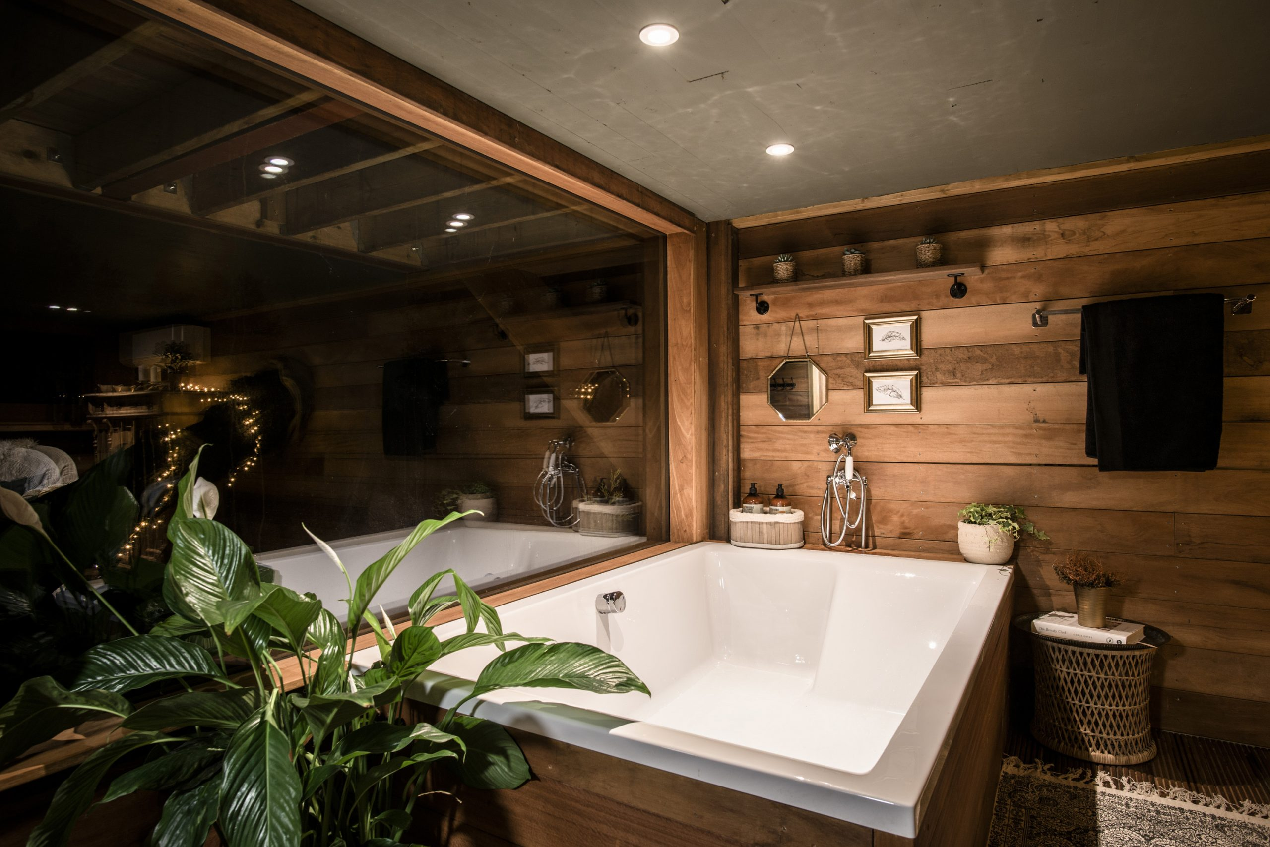 Nighttime photos showing the double bath and panoramic window in The Old Oak at Colemans Farm